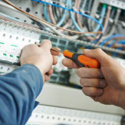 Hands of electrician with screwdriver tighten up switching electric actuator equipment in fuse box