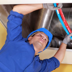 Worker holding blue and red pipes under air ducts